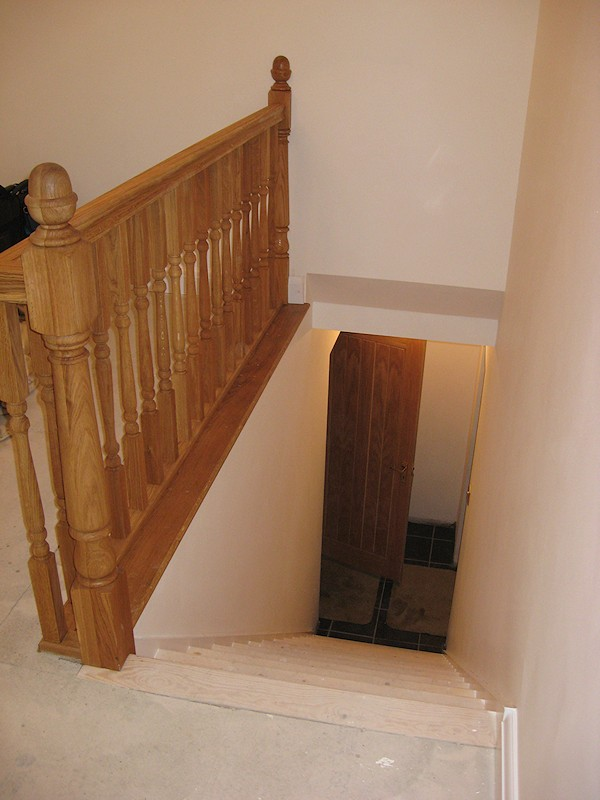 A simple straight flight staircase between enclosed walls, brought to life with oak balustrade on landing.