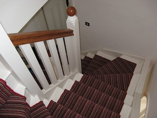 This softwood double winder staircase was for a loft conversion, painted white with a carpet runner.